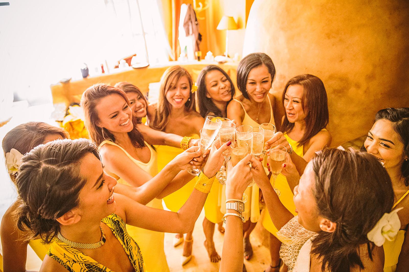 Mariage Mas de La Rouquette. David Pommier photographe de mariage. Les femmes et la mariée boivent le champagne pendant les préparatifs. Elles sont toutes habillées en jaune. Toutes venues de Singapour