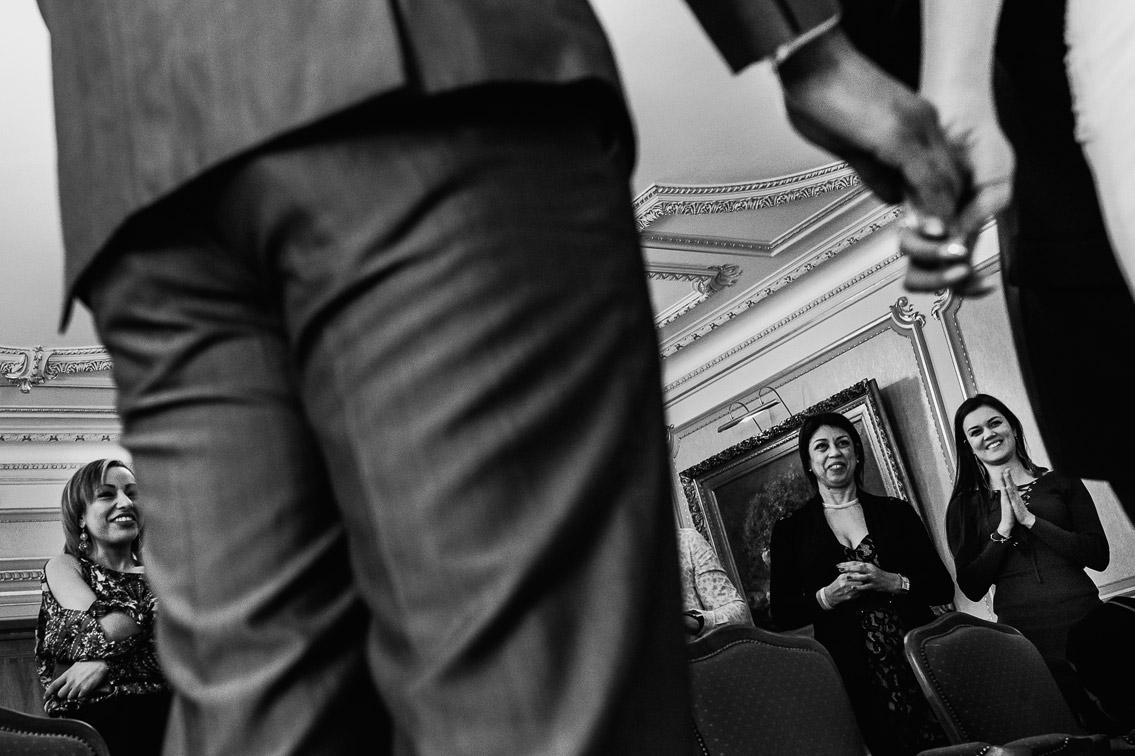 Photo de mariage à la mairie Lyon 6eme. Le regard des amis, famille après l'échange des voeux des mariés qui se tiennent par la main