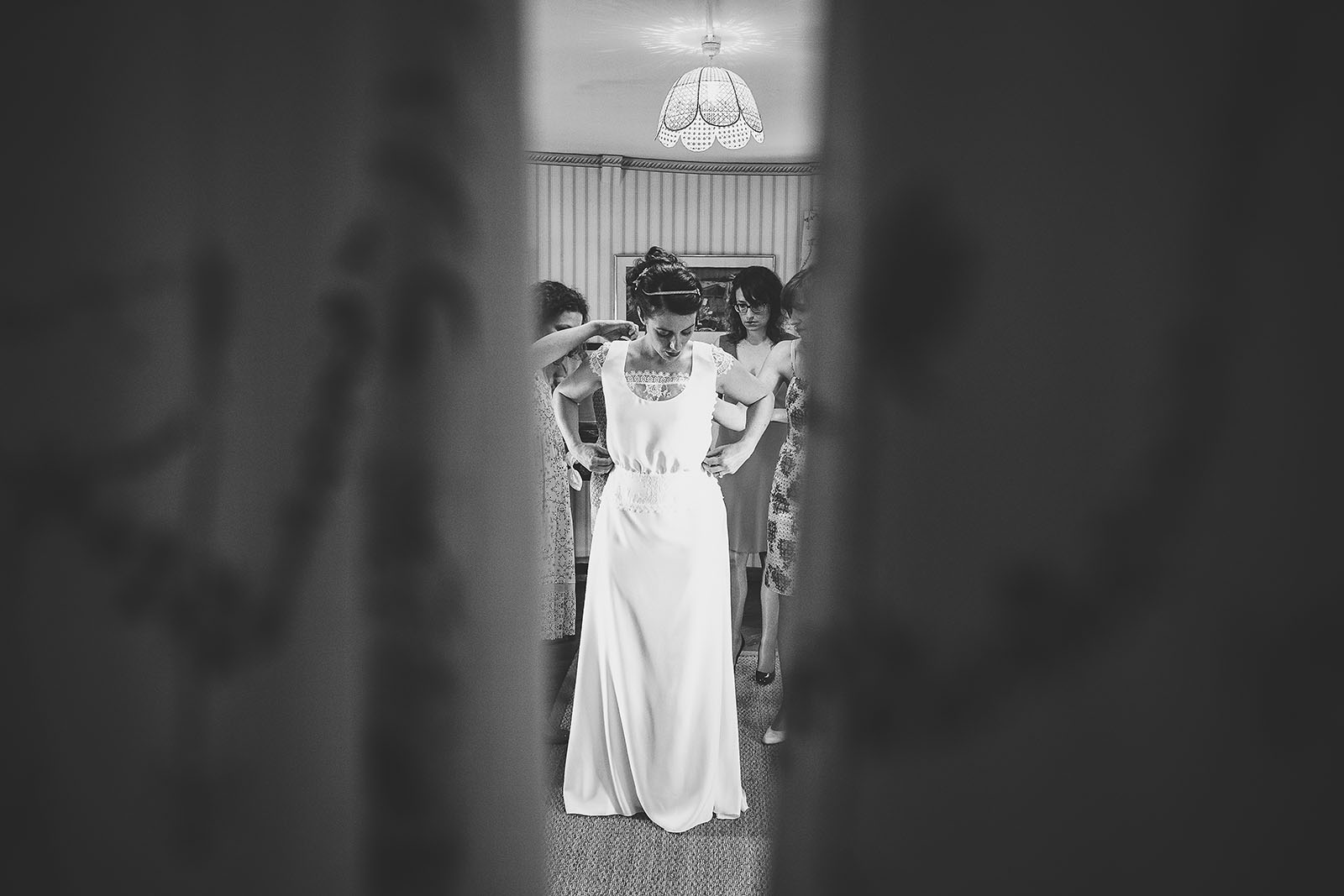 Mariage Château de Beauvoir. La mariée met sa robe avec l'aide de ses amies et témoins. David Pommier photographe de mariage