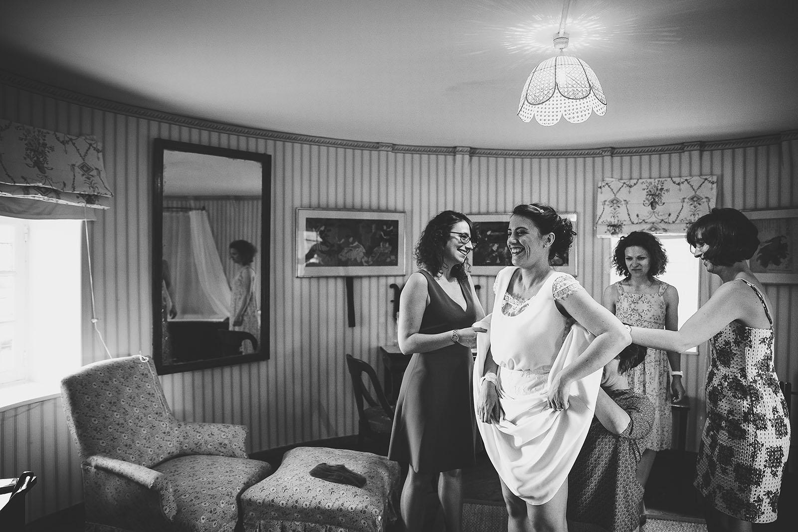 Mariage Château de Beauvoir. Les préparatifs de la mariée. Mettre sa robre avec ses amies. David Pommier photographe de mariage