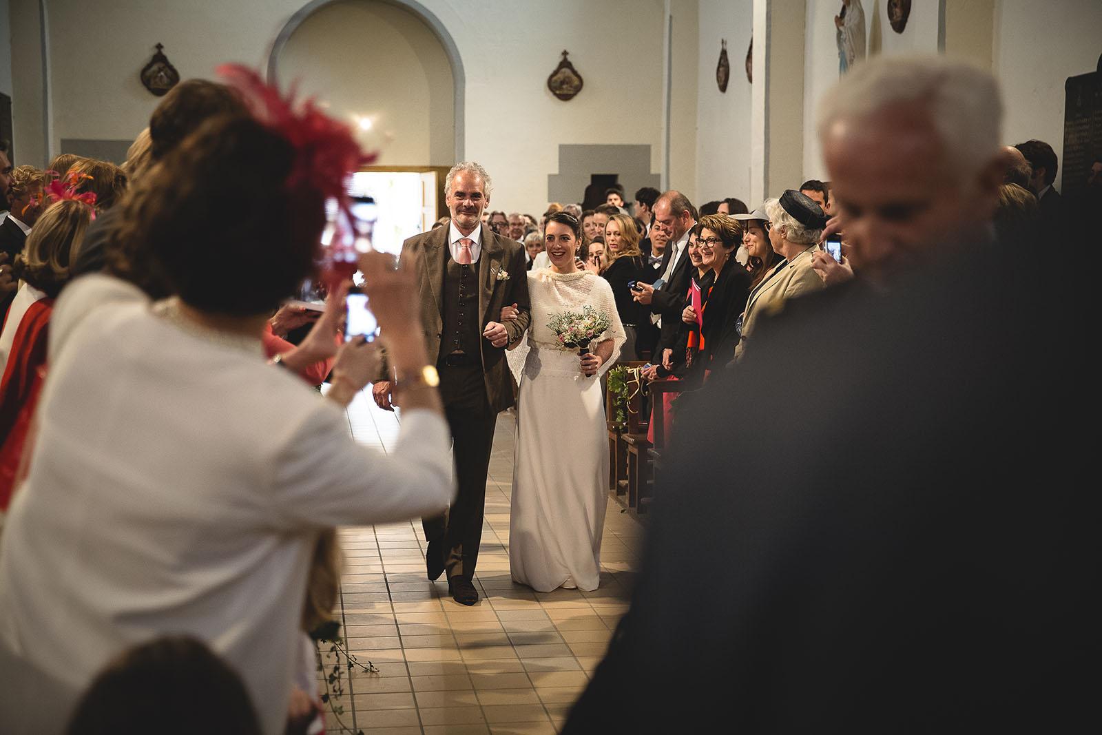 Mariage Château de Beauvoir. L'entrée de la mariée dans l'église au bras de son père. David Pommier photographe de mariage
