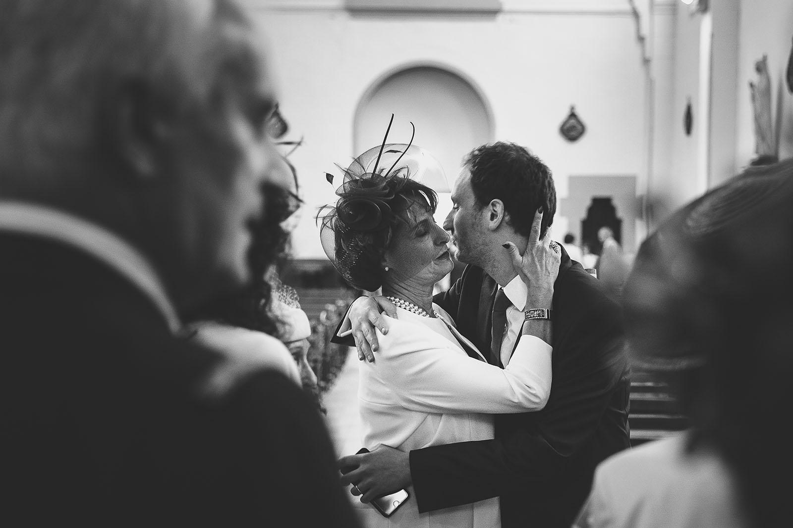 Mariage Château de Beauvoir. La maman du marié le prend dans ses bras à l'église. David Pommier photographe de mariage