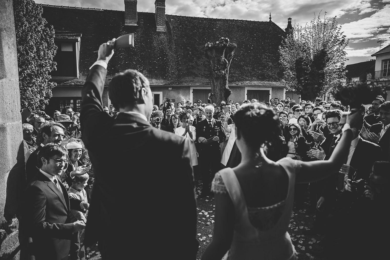 Mariage Château de Beauvoir. La sortie de l'église des mariés sous les applaudissements des familles et des amis. David Pommier photographe de mariage Saint Pourçain sur Besbre Allier