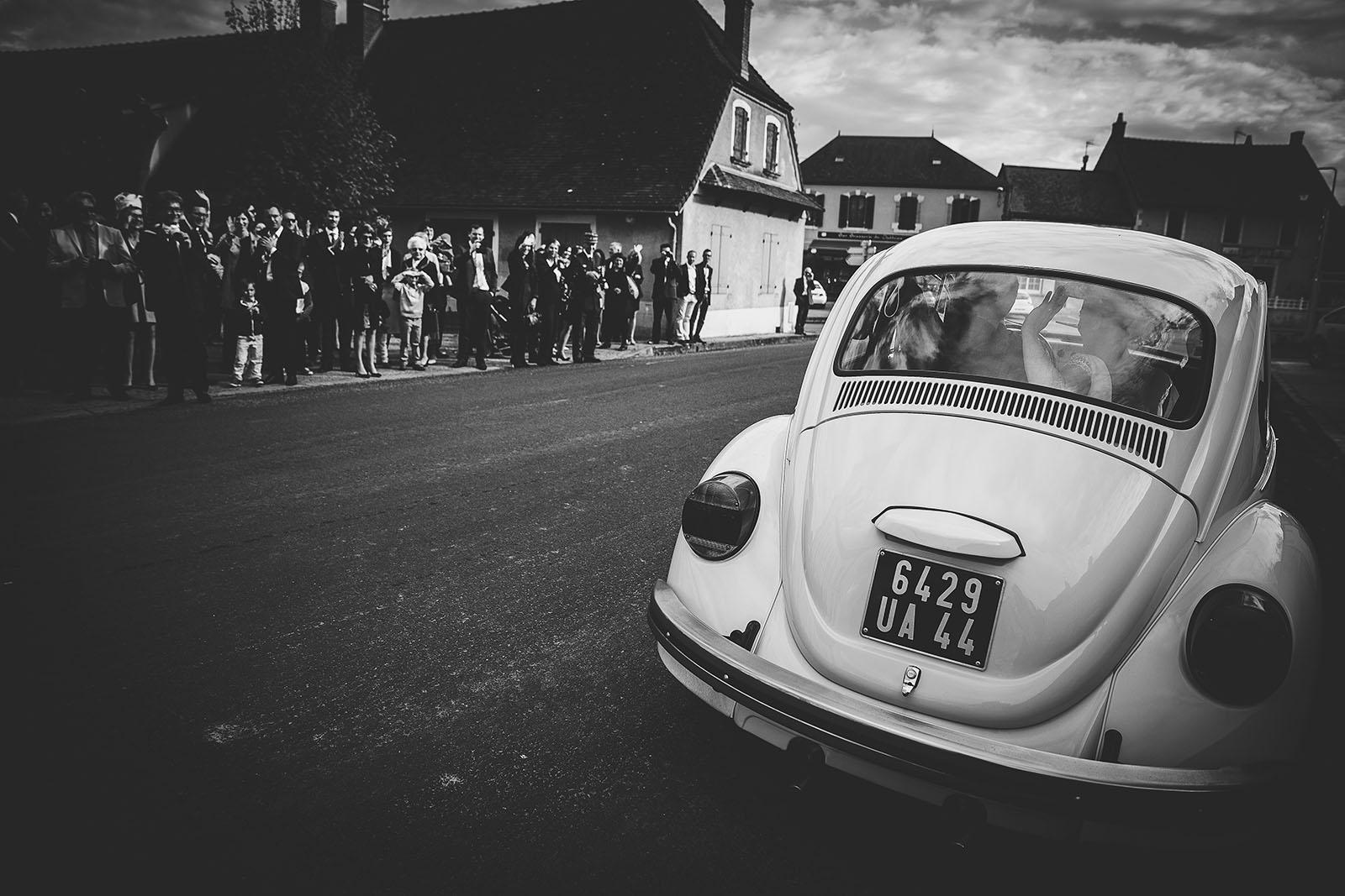 Mariage Château de Beauvoir. Départ des mariés de l'église dans une belle voiture Coccinelle blanche. David Pommier photographe de mariage