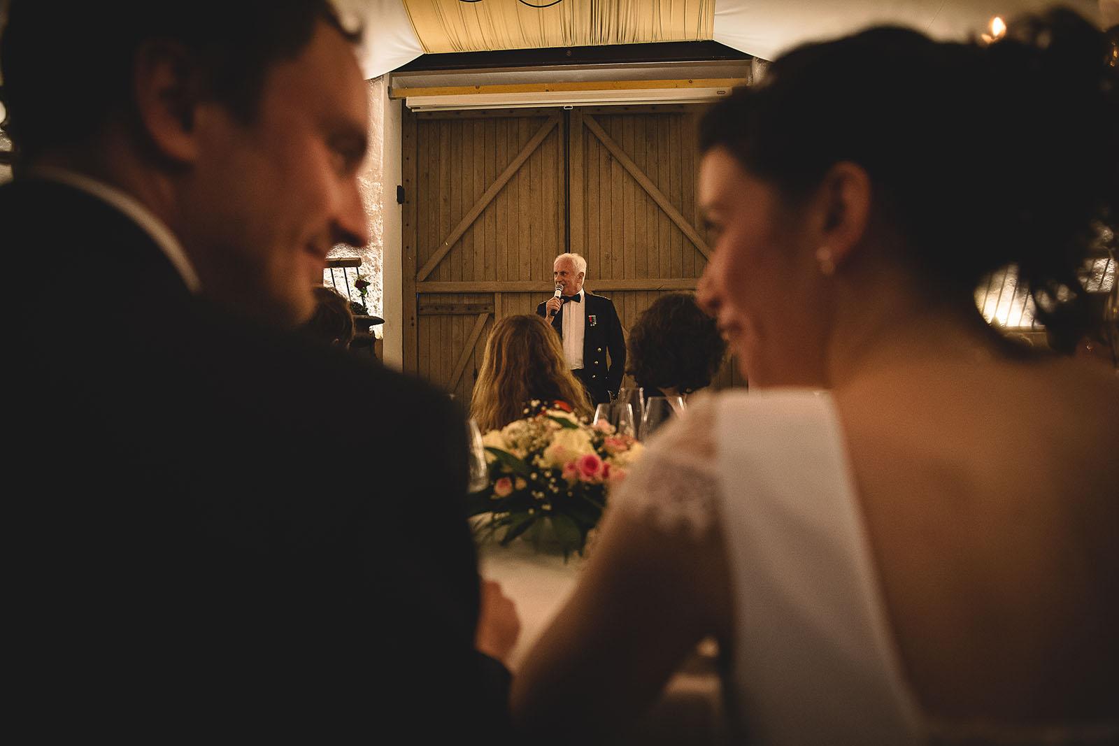 Mariage Château de Beauvoir. Portrait du père du marié qui fait un discours avec les mariés en premier plan. David Pommier photographe de mariage