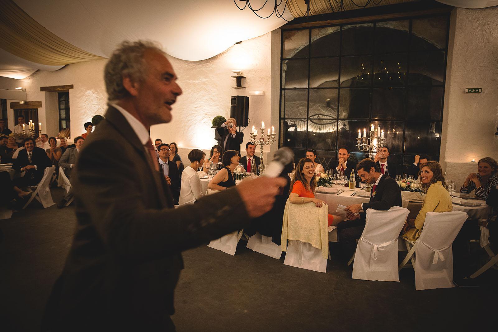 Mariage Château de Beauvoir. Le père de la mariée fait un discours dynamique devant la table des mariés. David Pommier photographe de mariage