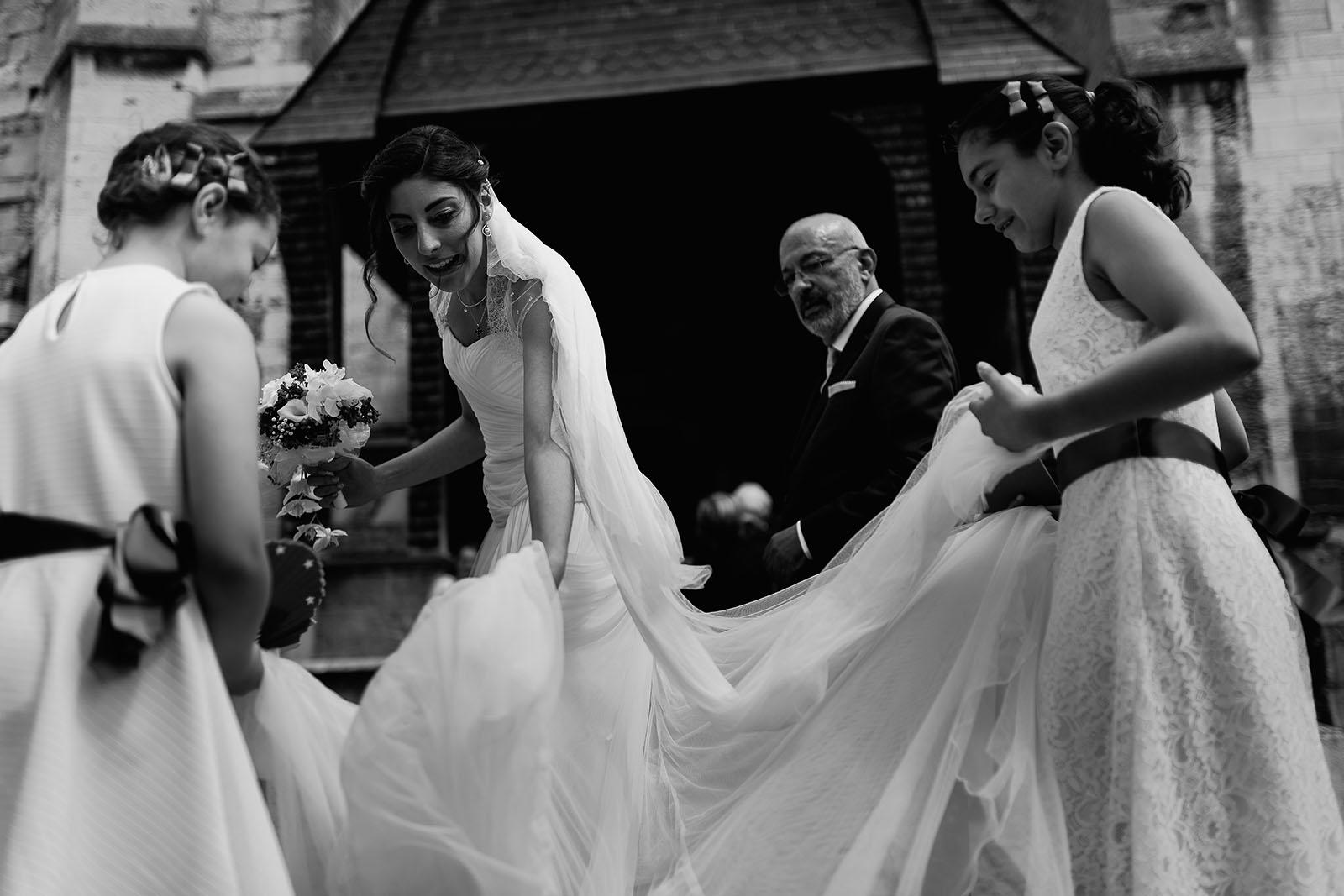Mariage au Manoir de Corny en Normandie. Les demoiselles d'honneur remettent correctement la robe de la mariée