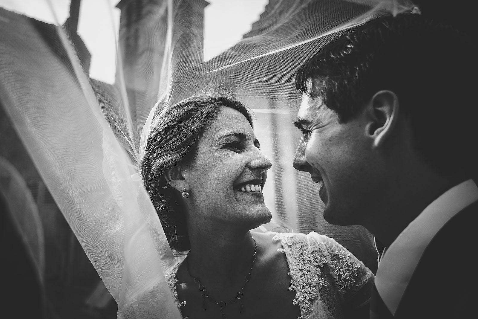 Mariage témoignage de la marié contente de son photographe. Le mariage a eu lieu à Lyon il s'agit d'une photo de couple sous le voile devant l'église. David Pommier photographe de mariage à Lyon