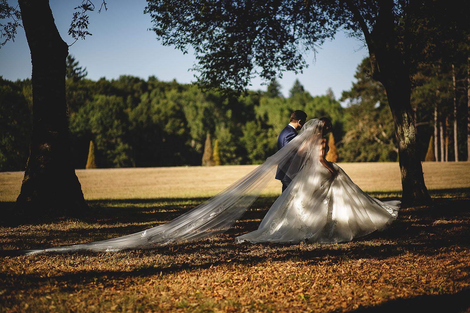 Mariage au Château de Beguin David Pommier photographe de mariage. Les mariés marchent dans le parc du château