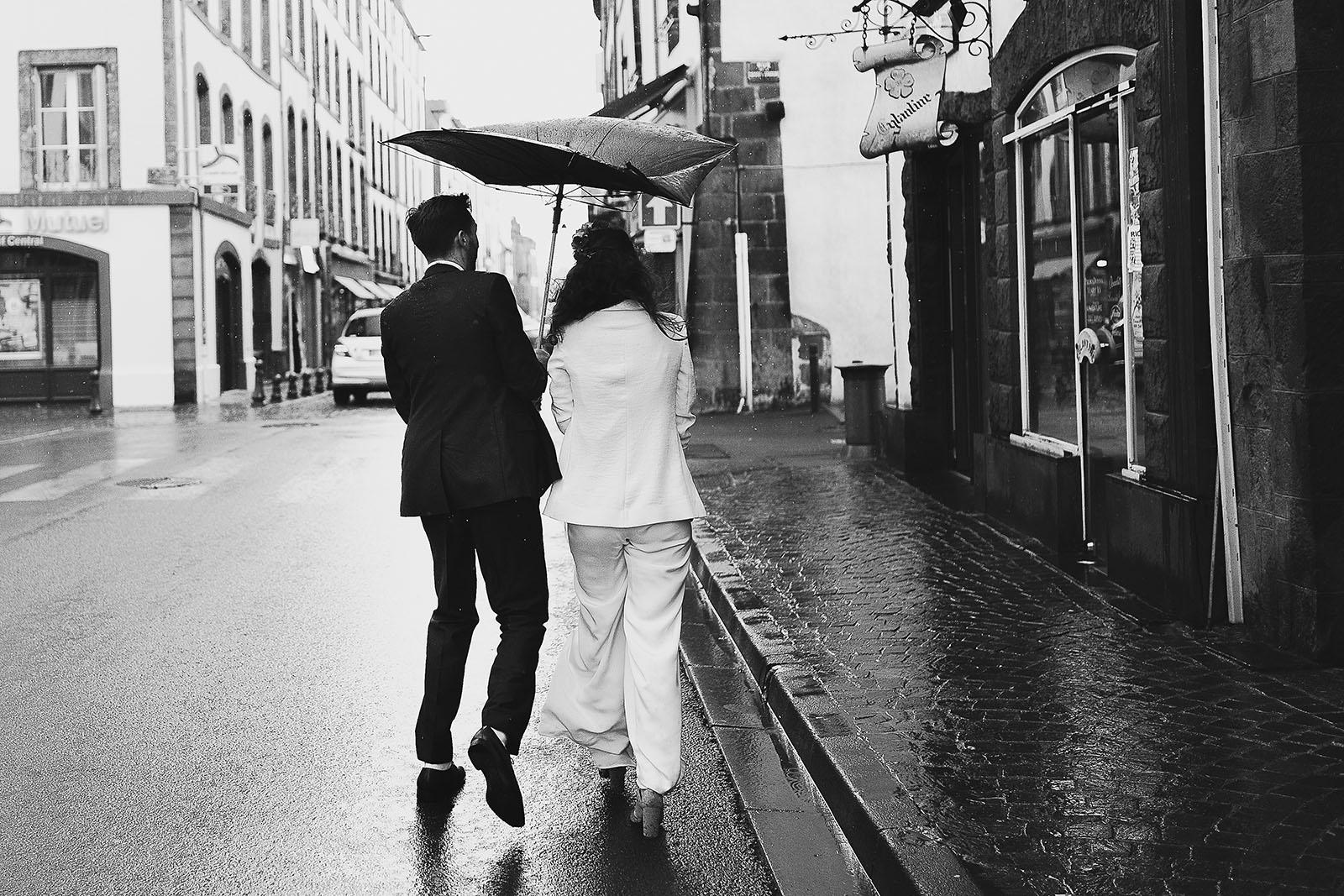 Photographe de mariage à Clermont Ferrand Les mariés sous la pluie avec le parapluie