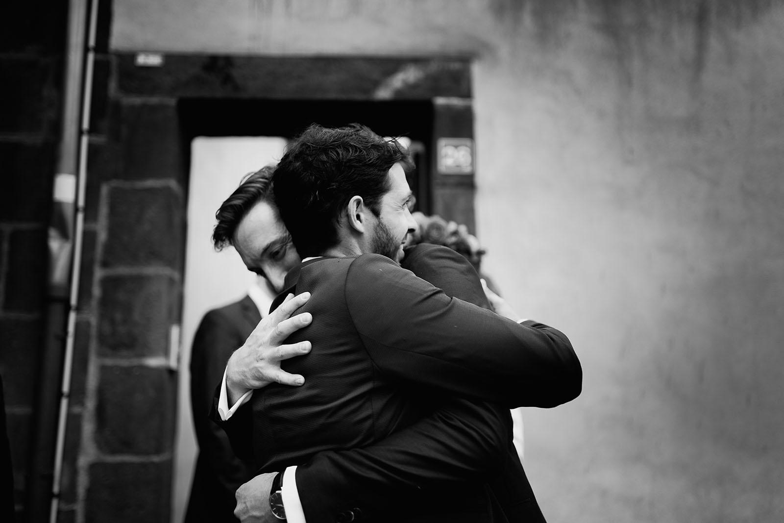 Photographe de mariage à Clermont Ferrand Le marié prend dans ses bras un témoin