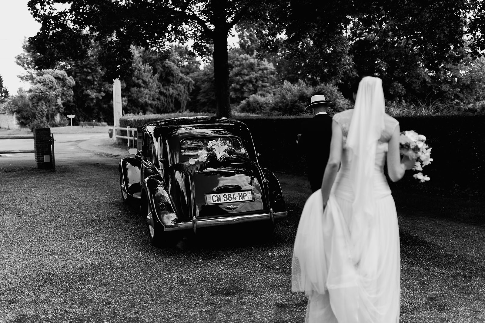 Mariage au Manoir de Corny en Normandie. La mariée rejoint sa voiture traction