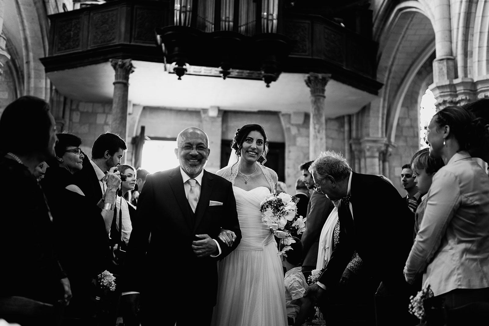 Mariage au Manoir de Corny en Normandie. Entrée de la mariée dans l'église au bras du papa