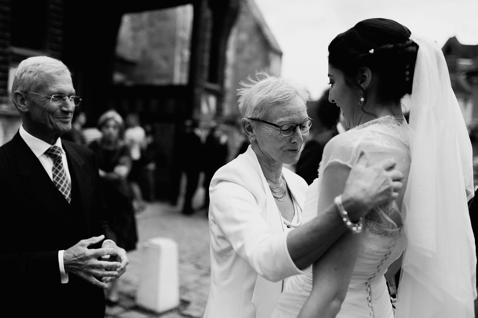 Mariage au Manoir de Corny en Normandie. La mariée et ses grands parents à la sortie de l'église