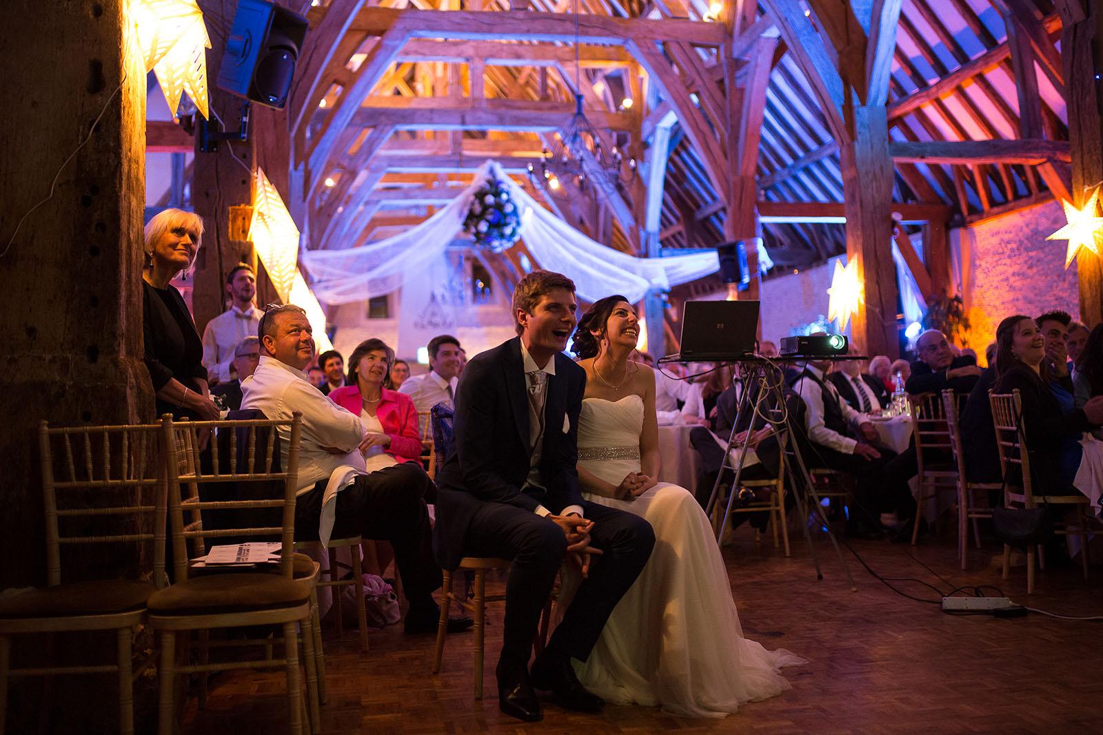 Mariage au Manoir de Corny en Normandie. Les mariés regardent une vidéo surprise