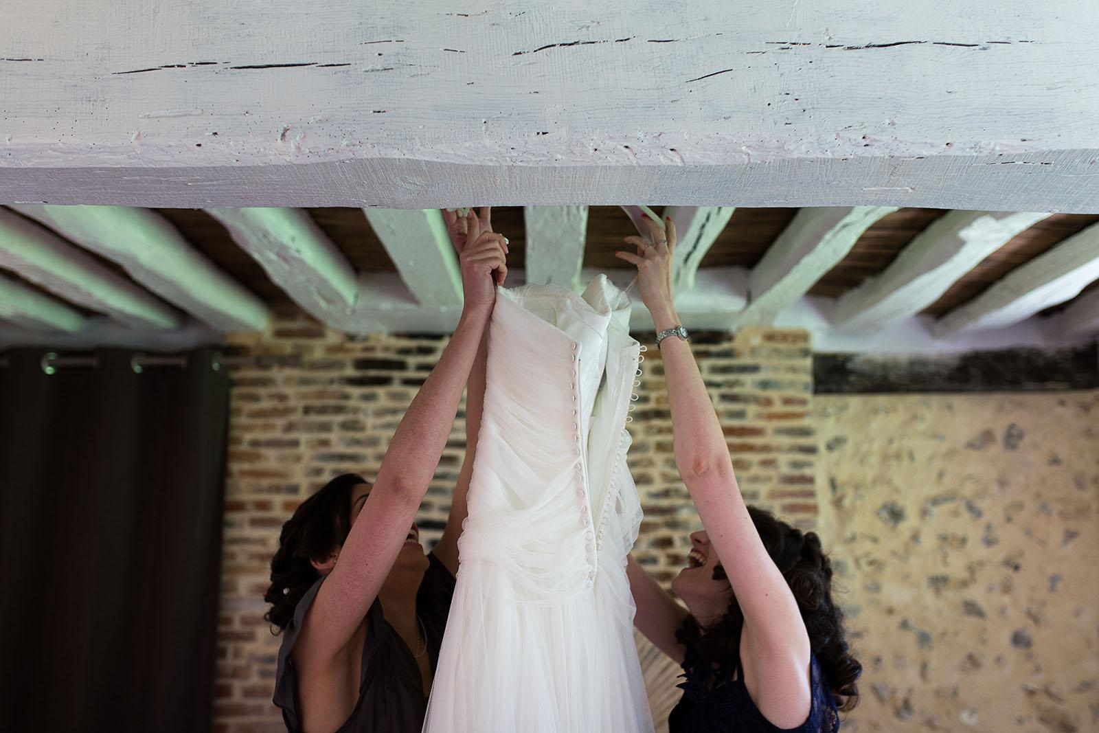 Mariage au Manoir de Corny en Normandie. Décrochage de la robe de la mariée
