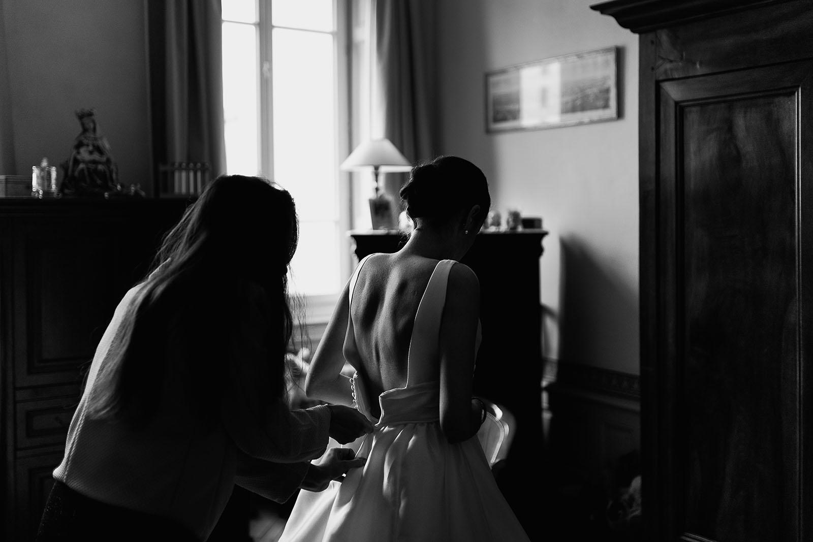 Photographe de mariage à Lyon. Fermeture de la robe de la mariée