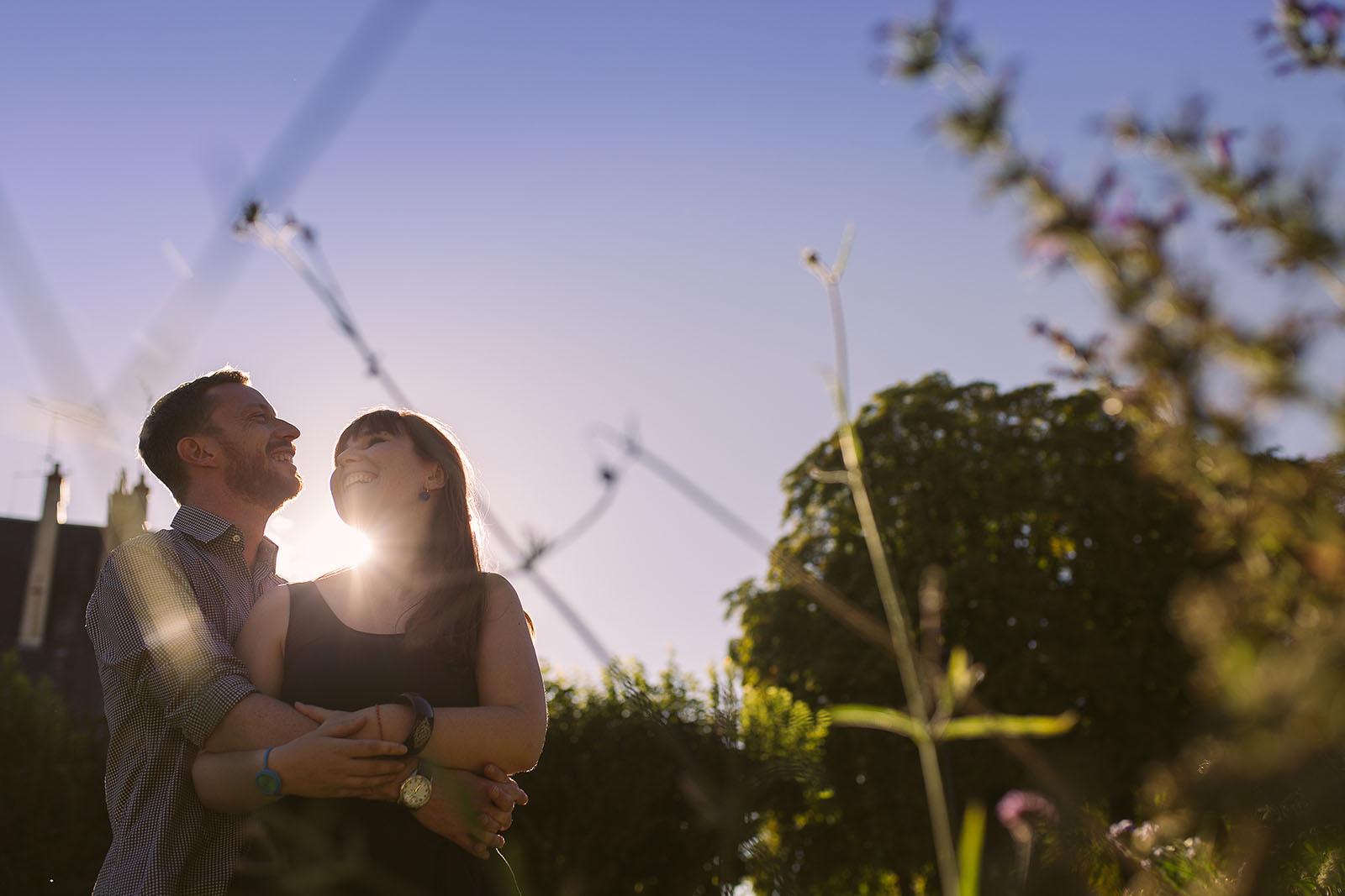 Photographe de mariage château le sallay nevers Love session ou séance d'engagement à Paris d'une jeune couple qui rient ensemble. Photo à contre jour avec une belle lumière et le soleil