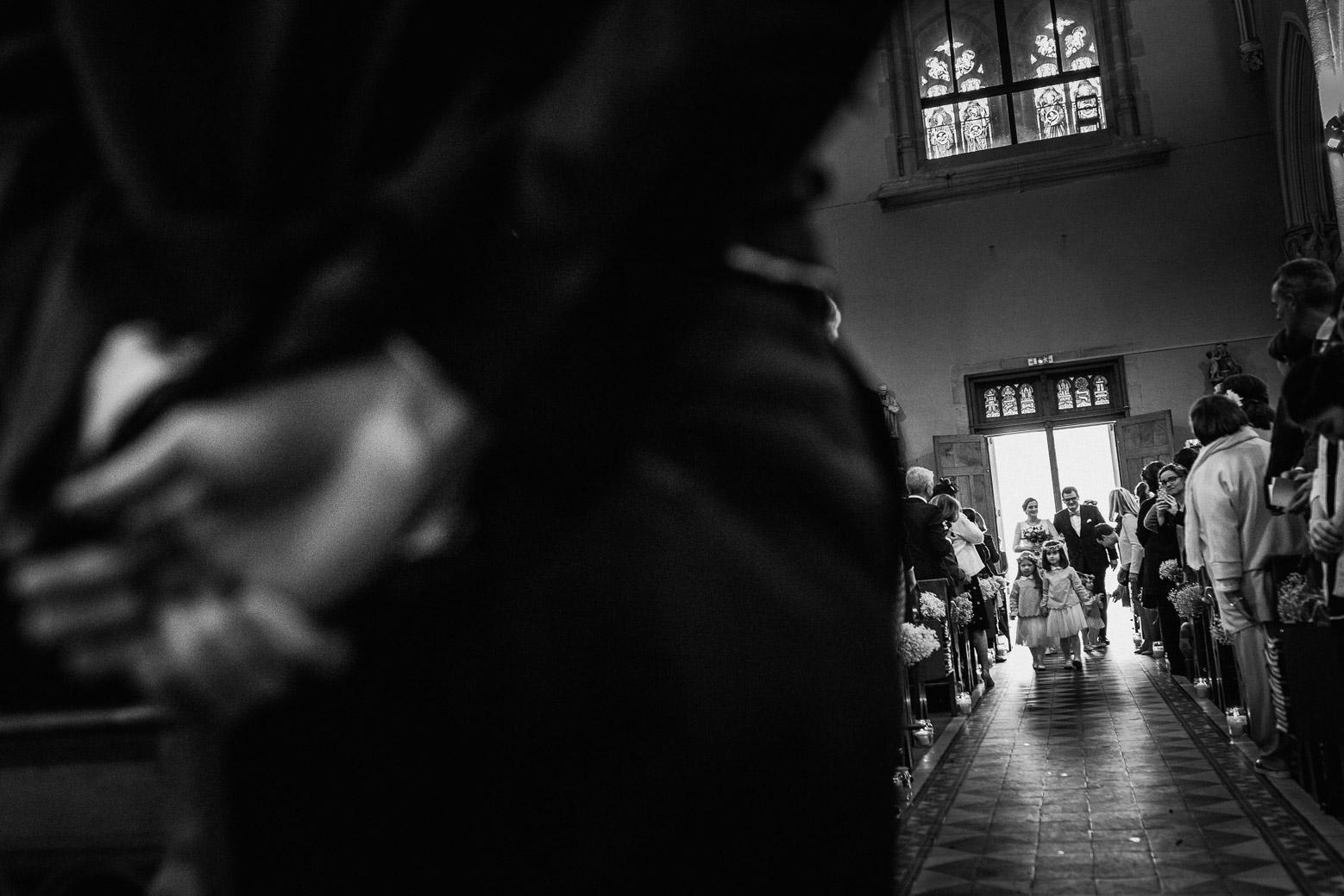 Reportage photo de mariage à Lyon - Manoir de la Garde. Le marié attend la mariée qui entre dans l'église