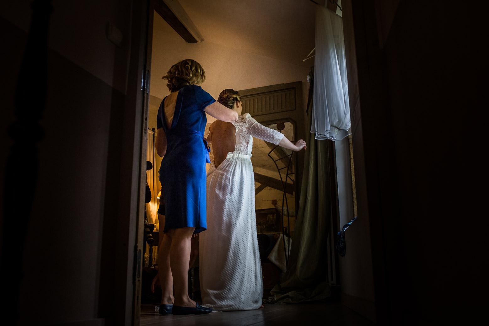 Reportage photo de mariage à Lyon - Manoir de la Garde. La mariée enfile sa robe