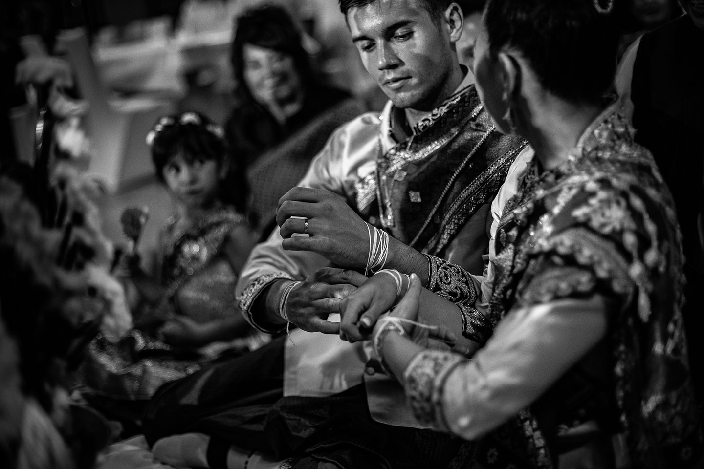 Les mariés relient les fils de coton durant la cérémonie khouane laotienne