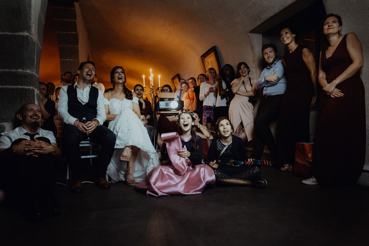 Meilleures photographies de mariage du photographe de mariage David Pommier. Château de Saulnat. Photographie de mariage lors de la soirée durant la vidéo projection surprise. Comment choisir son photographe de mariage. Et pourquoi?